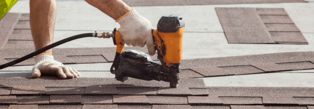 Residential roofing contractor putting the asphalt roofing (shingles) with nail gun